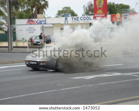 fire brigade attending burning porsche - stock photo