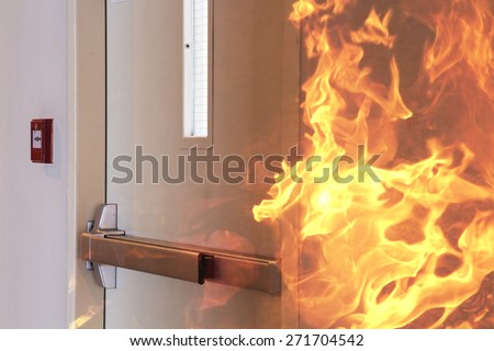 Fire burning in front of the closed door. - stock photo