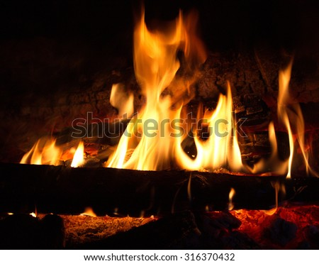 Fire burning wood to wood in the dark