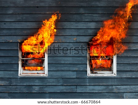 Fire bursts through two windows on the side of a house. - stock photo