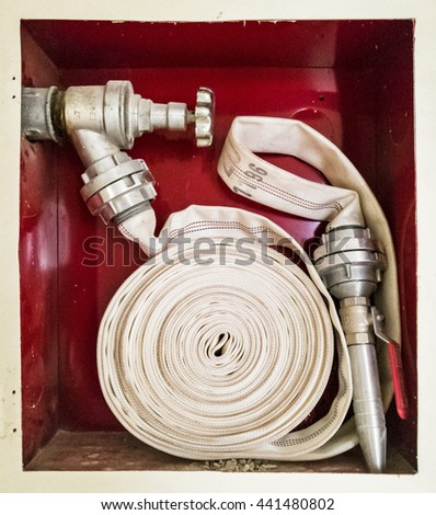 Fire cock with stacked hose. Water tap. Modern system. Iron hydrant valve. Socket for connection of fire hose. - stock photo