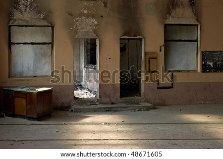 Fire damaged room. Black burnt out wood. Pastel painted walls. Dramatic light. Photo taken with Leica M9. - stock photo