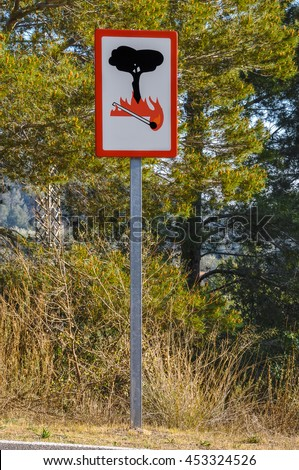 Fire danger sign (no campfires sign) at the side of the road near the mountain forest. Catalonia, Spain. Vertical.