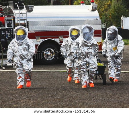 Fire departments & emergency response teams conduct disaster preparedness drills. This HAZMAT team is suited up with PPE to protect them from hazardous materials as they investigate this disaster. - stock photo