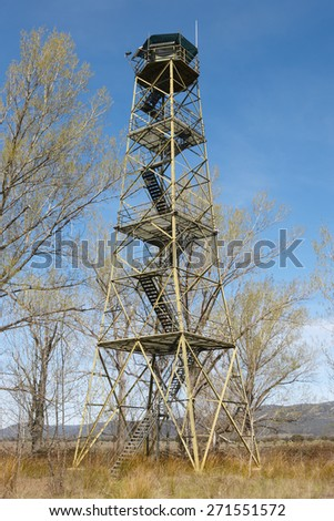 Fire detection watch tower surrounded by deciduous trees in Spain. Vertical - stock photo