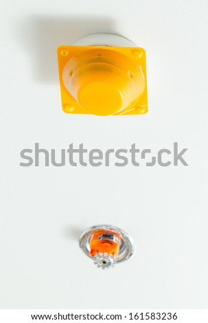 Fire detector and extinguisher with white ceiling as background - stock photo