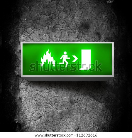 Fire emergency exit sign on a grunge obsolete wall - stock photo