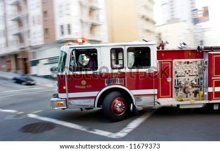Fire engine in a big city on it's way to an emergency call with sirens and lights on - stock photo