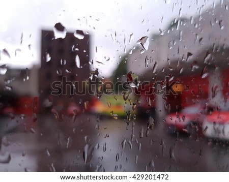 Fire engines at a fire station in the rain from behind a glass covered in raindrops background - stock photo