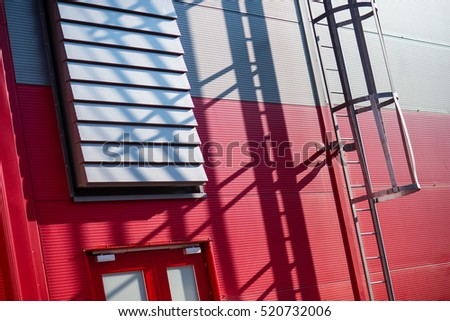 Fire exit from the red and blue building. Outdoor iron stairs.