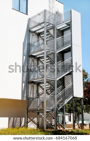 Fire Exit. Metal Fire Escape Outside Ladder On Modern Apartment Building  For Emergency. Fire
