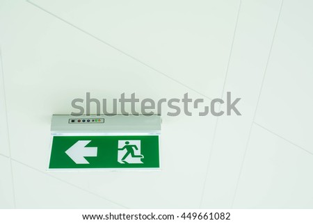Fire exit sign on the wall  - stock photo