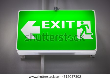 Fire exit signs green wall. Fluorescent light - stock photo