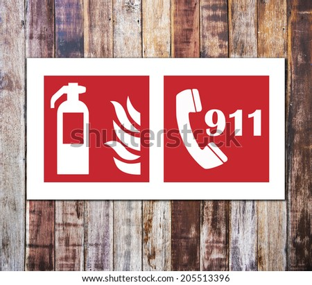 Fire extinguisher sign and 911 emergency isolated on wooden wall - stock photo