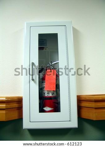 Fire extinguisher, white cabinet - stock photo