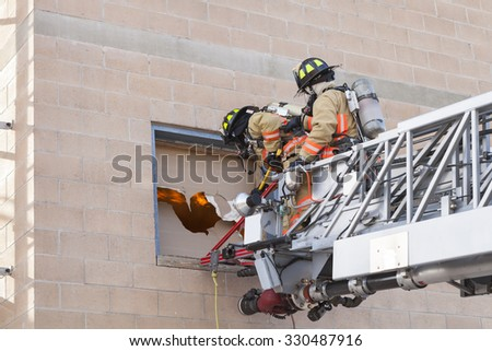 Fire Fighters breaking in window during training exercise. - stock photo