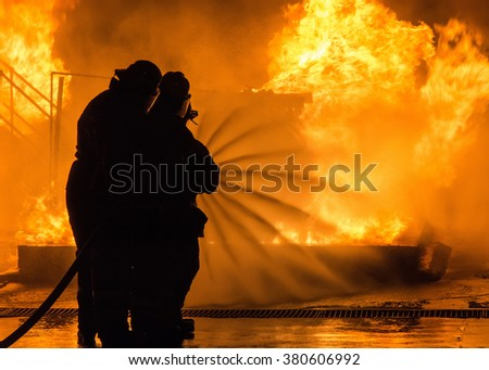 Fire fighters extinguishing blazing fire