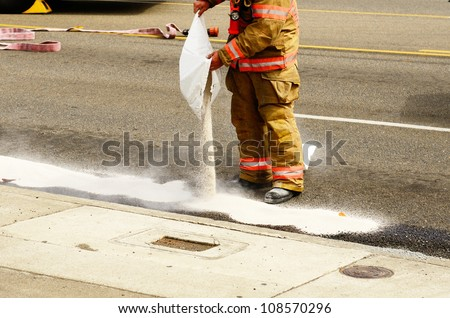 Fire fighters spreading absorbant at a four vehicle accident involving two large trucks resulted in a single injury and a diesel fuel spill. July 17, 2012 in Roseburg Oregon - stock photo