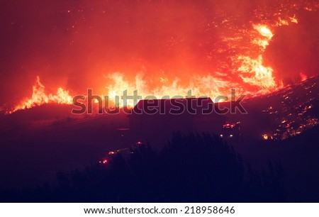 Fire fighters try to save a home from forest fire as flames rapidly approach the house.   The Carlton Complex fire - WA state's biggest wild fire in history.  100's evacuated and dozens of homes lost - stock photo