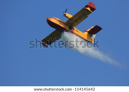 Fire-fighting aircraft drops water - stock photo