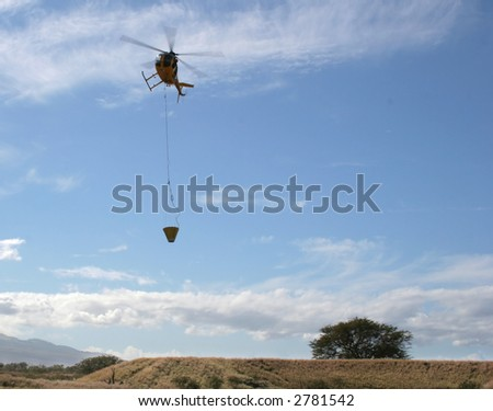 Fire-fighting helicopter in flight with water bucket responding to an emergency - stock photo