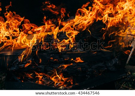 Fire flame against the dark backround - stock photo