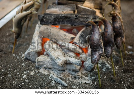 Fire for Grilled fish yakitory , Japanese street food, Close up fire with raw japan fish ayu grill on roaster