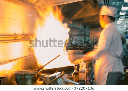 Fire hard cooking with chef in kitchen,motion blur - stock photo