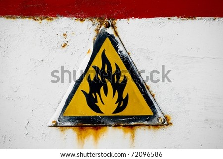 Fire hazard sign on an old metal surface - stock photo