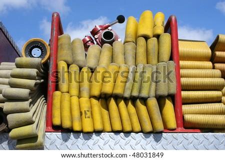 fire hose folded up on fire engine - stock photo