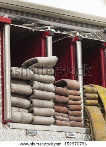 Fire hoses folded in fire truck. - stock photo