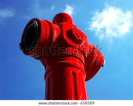 Fire hydrant on a blue sky  with white clouds background - stock photo