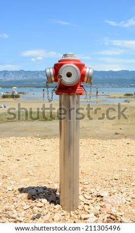 Fire hydrant on the seashore: - stock photo