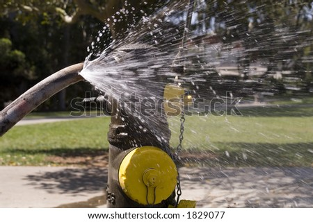 Fire hydrant with a leaky hose on a warm summer day. - stock photo