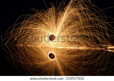 fire in the dark. spinning fire on the dock at the lake. - stock photo