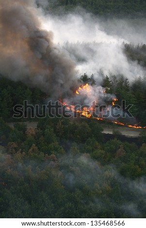 fire in the forest of wildfire photographed from a helicopter - stock photo