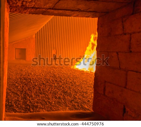 fire inside the coal boiler grate - view through hatch - stock photo