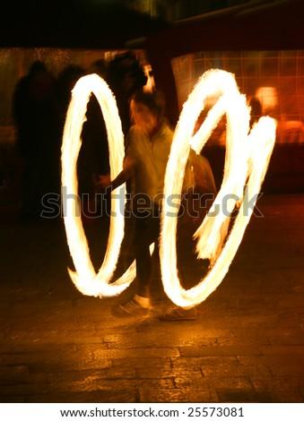 Fire juggler light trails during Venice carnival - stock photo