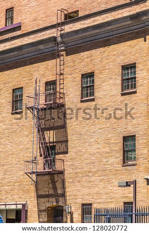fire ladder at an old Brick house - stock photo
