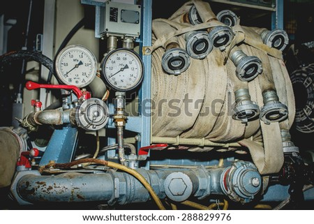 fire pump with pressure sensors sleeves and red cranes - stock photo