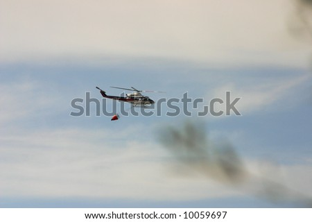 Fire rescue helicopter on its way with brown smoke from forest on fire - stock photo