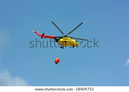 Fire rescue helicopter with water bucket with copyspace. All copyrighted elements removed - stock photo