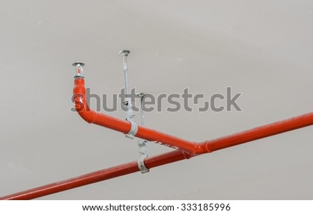 Fire sprinkler and red pipe hanging on white ceiling background - stock photo