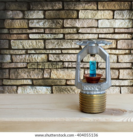fire sprinkler with fire on wooden and stone wall background. - stock photo