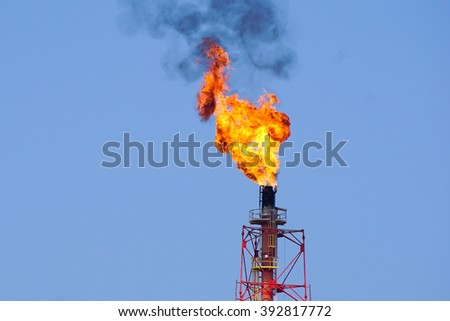 Fire torching against the sky burning gas flaring Gas or flare burn on offshore platform.  - stock photo