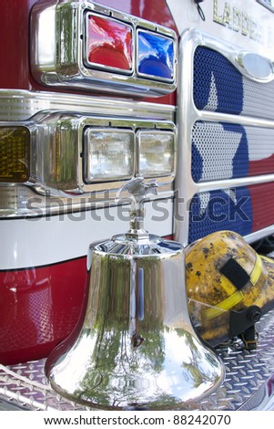 fire truck with bell and hat on the bumper - stock photo