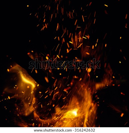 fire with sparks on a black background - stock photo