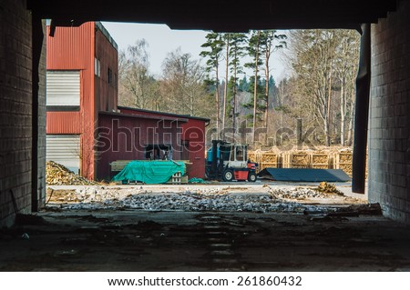 Fire wood industry seen from inside abandoned building. Walls frame the view. Fork lift and fire wood on pallets outside red building. Pile of timber under green tarp in front of building. - stock photo