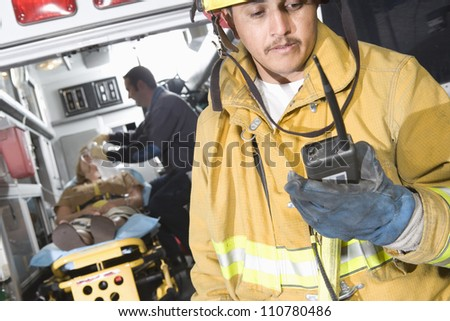 Fire worker holding walkie-talkie with patient and EMT doctor in the background - stock photo