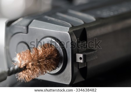 Firearm Maintenance - Brush Cleaning Bore of Gun - stock photo